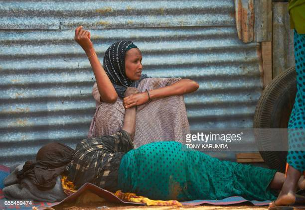 An elderly woman weakened by hunger lies on the ground as her daughter watches over her at a camp for the internally displaced on the outskirts of...