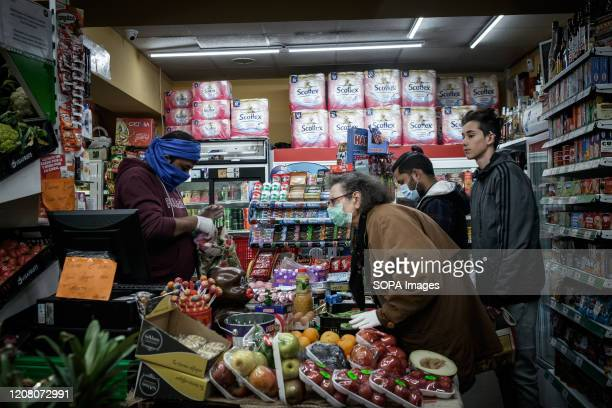 An elderly woman wearing a face mask as a precaution against the spread of Coronavirus buys food at a store during the coronavirus crisis Since the...