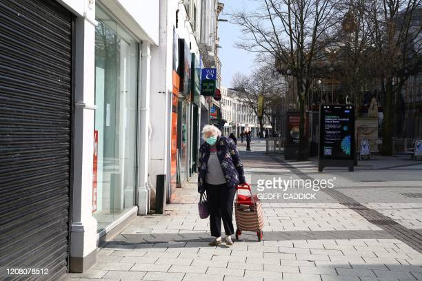 An elderly woman wearing a face mask as a precautionary measure against covid19 wheels her shopping troley past closed shops in Cardiff south Wales...