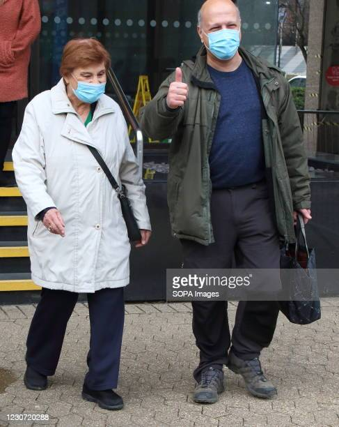 An elderly woman wearing a face mask, leaves the vaccination centre after receiving her first dose of the Astra Zeneca Oxford vaccine accompanied by...
