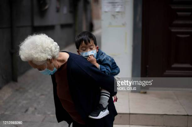 An elderly woman wearing a face mask piggybacks a boy along a street in Beijing on May 11, 2020.
