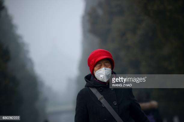 TOPSHOT An elderly woman wearing a mask closes her eyes as she walks at a park in Beijing on December 20 2016 Heavy smog suffocated northeast China...