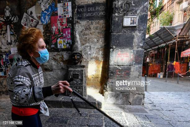 An elderly woman wearing a protective mask in the center of the city of Naples, after a government decree declaring all of Italy a protected area to...