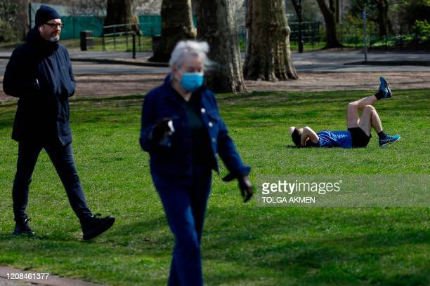 An elderly woman wears a mask as a precautionary measure against covid19 as people take their daily exercise in Battersea Park in London on March 28...