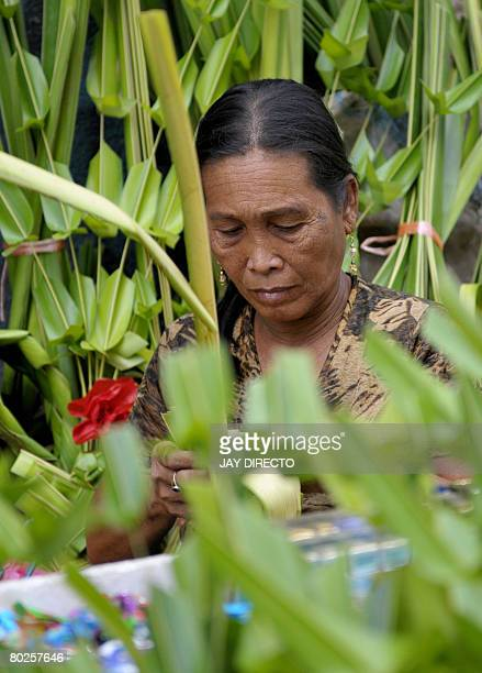 An elderly woman weaves palm branches into decorative creations to sell them on Palm Sunday in Manila on March 15 2008 The Palm Sunday mark the start...
