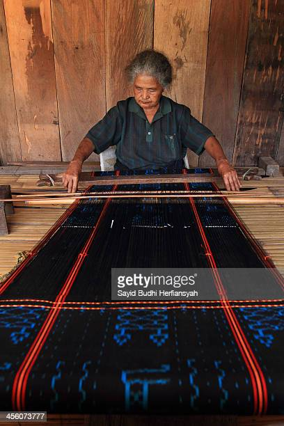 An elderly woman weaving Ikat at traditional house. Ikat is a style of weaving that uses a resist dyeing process on one of the warp before woven...