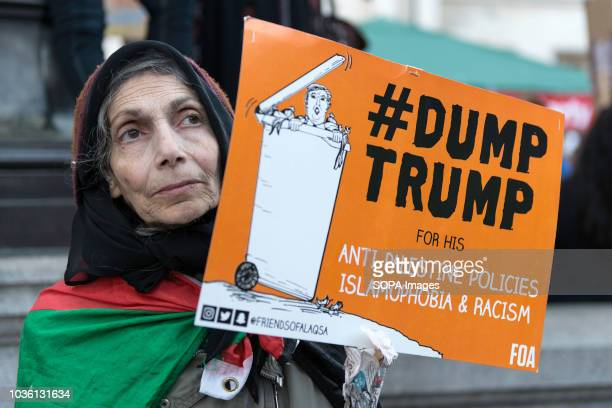 An elderly woman with a Palestinian flag on her shoulders was holding a banner reading #DUMPTRUMP Thousands of protesters marched in central London...