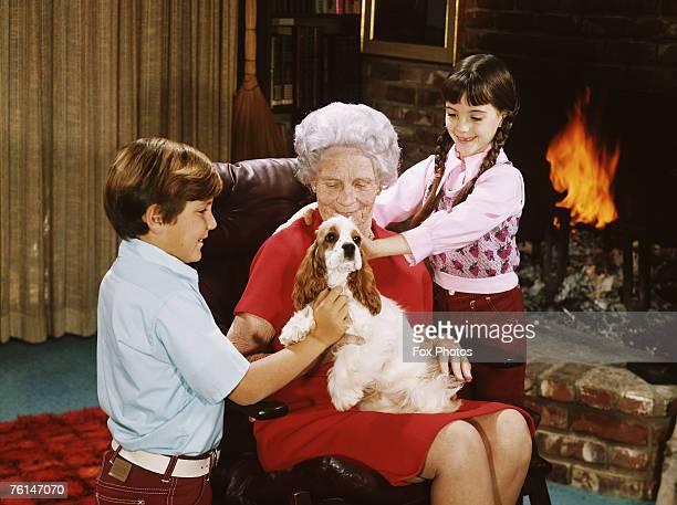 An elderly woman with her grandchildren and a pet spaniel circa 1975