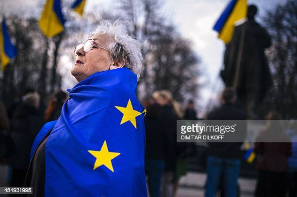 An elderly woman wrapped with an European Union flag attends a proUkraine rally in the eastern Ukrainian city of Lugansk on April 15 2014 Russia's...