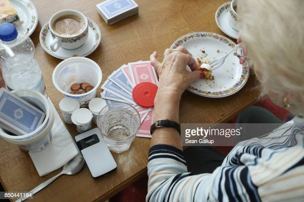An elderly women finishes eating a piece of cake while taking a break during a cards game of rummy at the Mireille Mathieu senior citizens' center on...