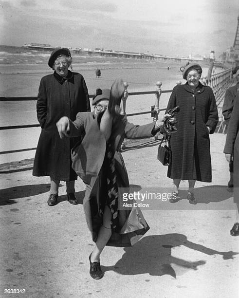 An elderly women performs a high kick on the promenade at Blackpool where an open invitation has been extended to pensioners in certain boroughs all...