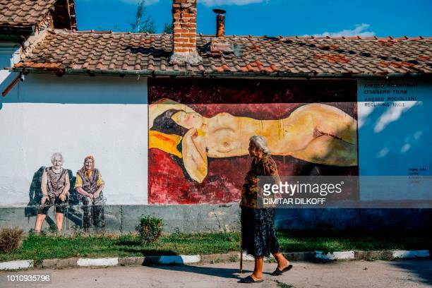 "An elderly women walks past a reproduction of Amedeo Modigliani's painting ""Reclining Nude"", painted on a wall of a house during an annual open-air..."