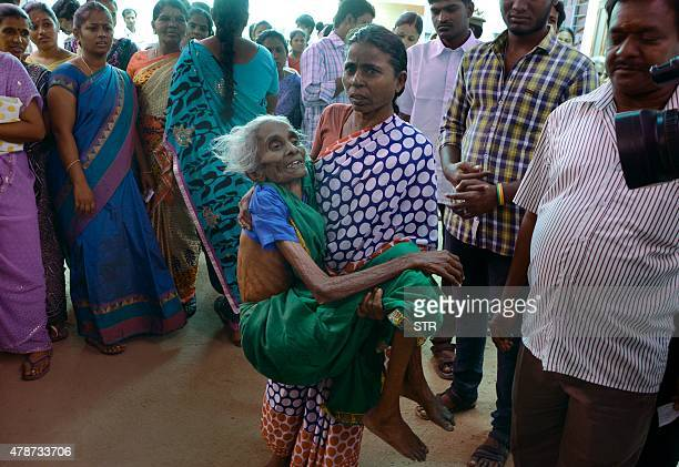 An eldery Indian voter is carried at a polling station during the byelection at R K Nagar in the southern city of Chennai on June 27 2015 A million...