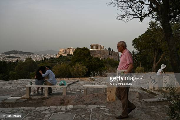 An eldery man passes by acouple kissing on a hill facing the ancient Temple of Parthenon atop the Acropolis hill in Athens on May 17, 2020 during the...