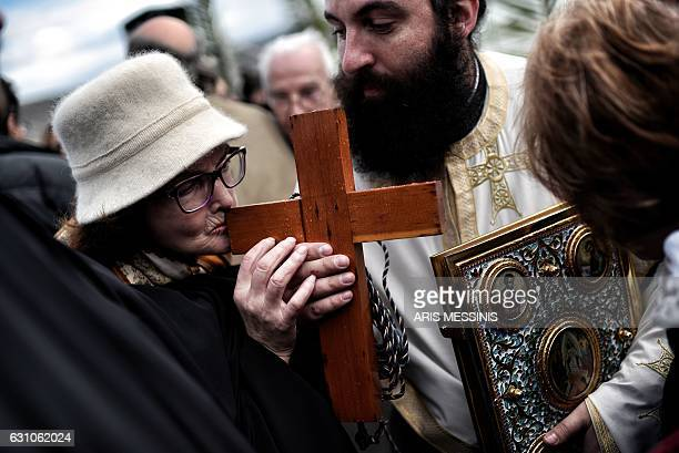 TOPSHOT An eldery woman kisses a wooden cross during a ceremony marking the orthodox Epiphany Day in a southern suburb of Athens on January 6 2017 As...
