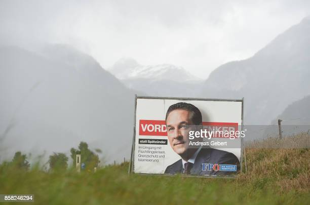 An election campaign poster of Heinz-Christian Strache of the right-wing Austria Freedom Party stands in front of the mountains next to a road on...