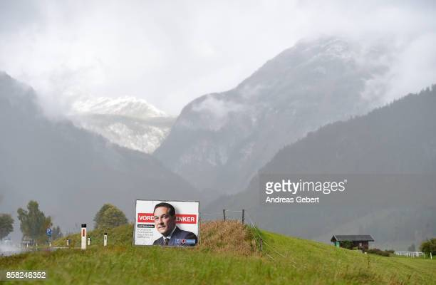 An election campaign poster of HeinzChristian Strache of the rightwing Austria Freedom Party stands in front of the mountains next to a road on...