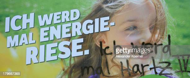 An election campaign poster of the German Green Party with the slogan 'When I grow up I will be an energy giant' has had the words spray painted 'I...