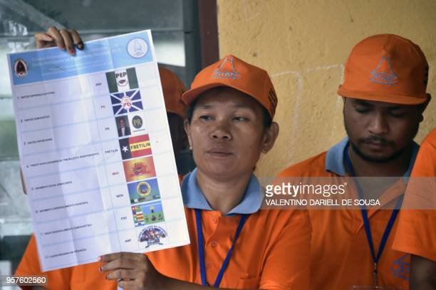 An election committee member holds up a ballot during vote tallying for the general election in Dili on May 12 2018 East Timor headed to the polls on...