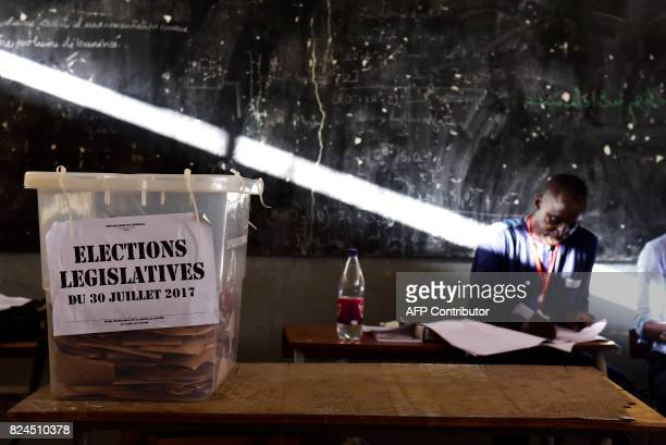 TOPSHOT An election helper sits next to an urn filled with ballots at a polling station in Dakar on July 30 during general elections Senegalese...