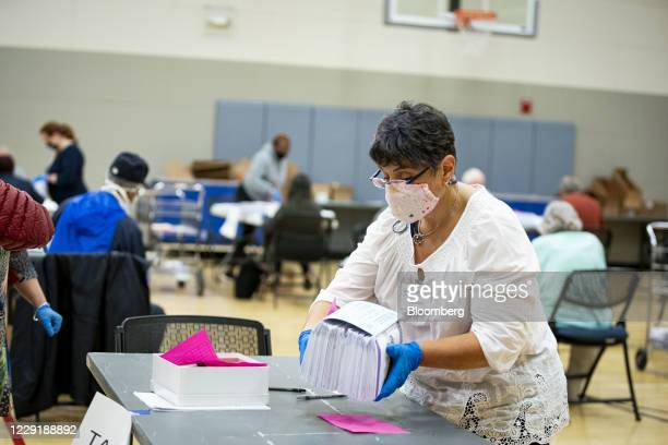 An election judge wearing a protective mask places a stack of mail-in ballots on a table before they are scanned by the Montgomery County Board of...