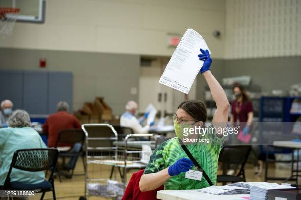An election judge wearing a protective mask prepares mail-in ballots to be scanned by the Montgomery County Board of Elections at a recreation center...