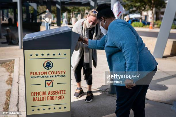 An election observer assists a voter as she drops off an absentee ballot into a drop box outside a polling location for the 2020 Presidential...
