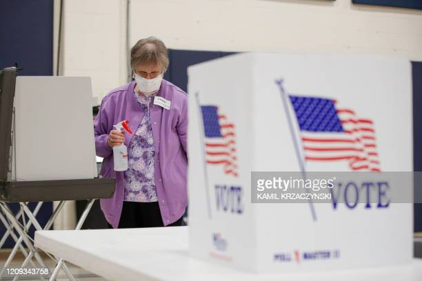 An election observer cleans voting booths during a Democratic presidential primary election at the Kenosha Bible Church gym in Kenosha, Wisconsin, on...