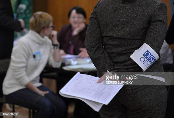 An election observer of the Organization for Security and Cooperation in Europe stands as electoral commission members count ballots at polling...