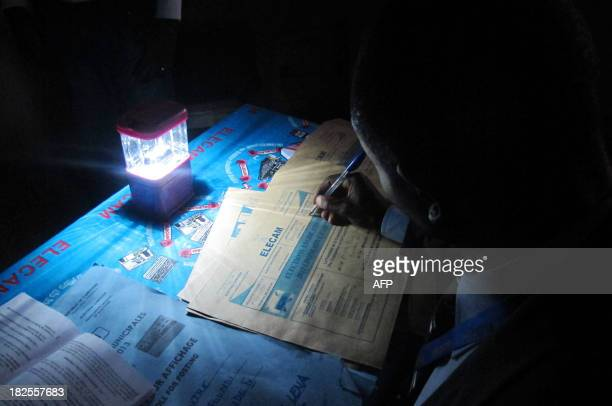 An election offical completes a document after counting ballot papers at a polling station in Yaounde on September 30 2013 for legislative and local...