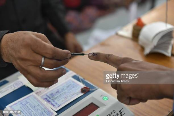 An election officer applies an indelible ink mark on the finger during voting at a polling station in Jahangirabad on November 28 2018 in Bhopal...