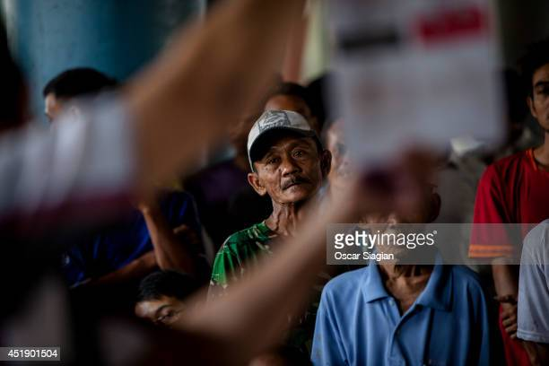 An election officer holds up the vote count at a polling station after the the Indonesia presidential election his ballot on July 9 2014 in Jakarta...