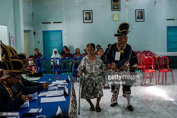 An election officer in traditional Kraton soldier known as 'Bergodo' costume helps an elderly woman votes at a polling station during the Indonesia...