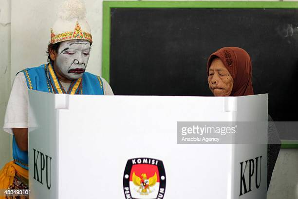 An election officer with Java costume helps an Indonesian woman as she casts her ballot for the Indonesia's legislative elections at a polling...