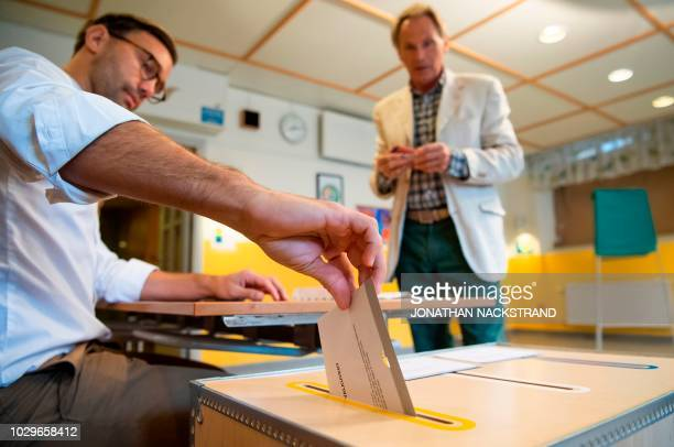 An election official casts a voter's ballot at a polling station during the Swedish general elections in Stockholm on September 9 2018 The polls...
