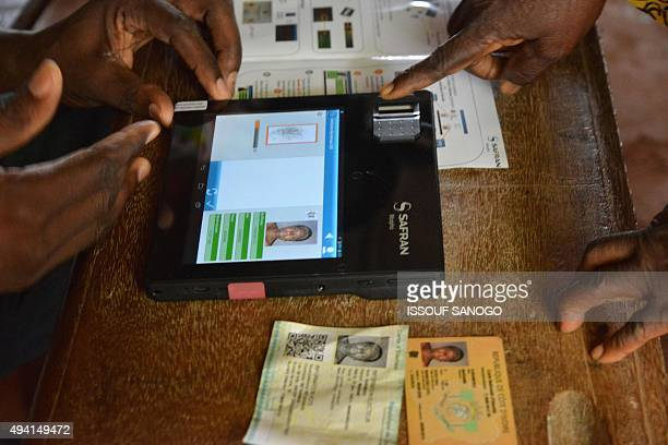 An election official checks the biometric identification information of a voter in the Ivory Coast presidential elections at a polling station on...