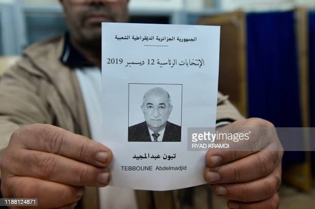 An election official displays a ballot paper of Algeria's presidential candidate Abdelmadjid Tebboune during the counting process in the capital...