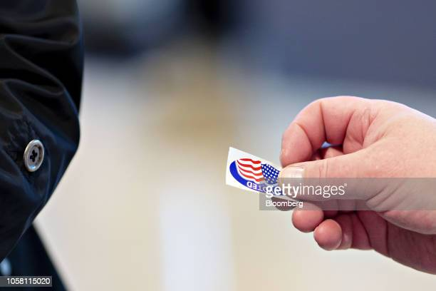"""An election official hands an """"I Voted"""" sticker to a voter at a polling station in Wauwatosa, Wisconsin, U.S., on on Tuesday, Nov. 6, 2018. The most..."""