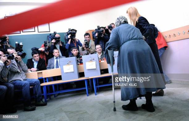 An election official helps an elderly woman to cast her vote during municipal elections at a voting centre in Istanbul on March 29 2009 Some 48...