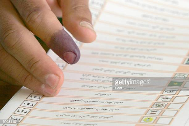 An election official moves ballot papers, his ink dyed finger signifying he has voted, January 30, 2005 in Basra, Iraq. Iraqis started voting in...