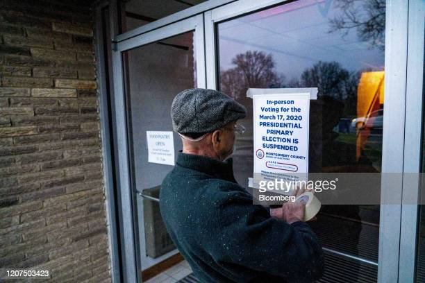 An election official places Presidential Primary Election Is Suspended signs on the doors of a polling station in Dayton Ohio US on Tuesday March 17...