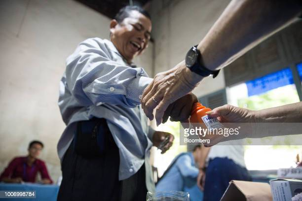 An election official right marks a voter's thumb after casting his ballot for the general election at a polling station in Phnom Penh Cambodia on...