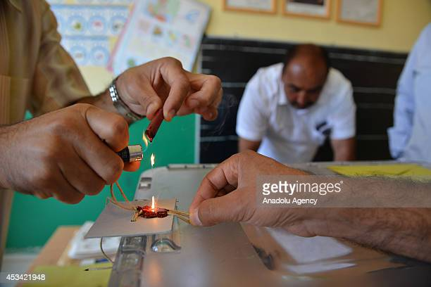 An election official seals a ballot box before the start of voting for the Turkey's Presidential election at the polling station in Edremir district...