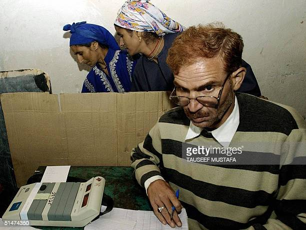 An election official sits in a polling station as two Kashmiri Muslim women cast their vote for a by-election, at Lawaypora in the Batamaloo...