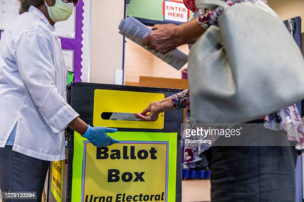 An election official wearing a protective mask assists a voter cast a ballot in a drop off box at an early voting polling location for the 2020...
