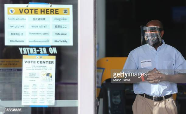 An election official wears a face shield and mask at a Vote Center located at the Staples Center on the first weekend of early in-person voting on...