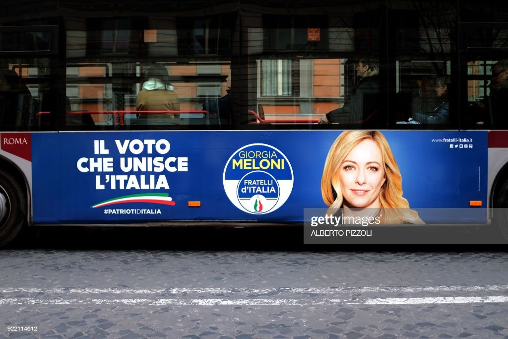 An election poster for the Fratelli D'italia (Brothers of Italy) party is seen on the side of a bus in Rome on February 21, 2018 ahead of the March 4 general elections. Italy heads to the polls next month to vote in a crowded general election, against a backdrop of populist gains in Europe, and the shadow of ex-leader Silvio Berlusconi still looms large. / AFP PHOTO / Alberto PIZZOLI
