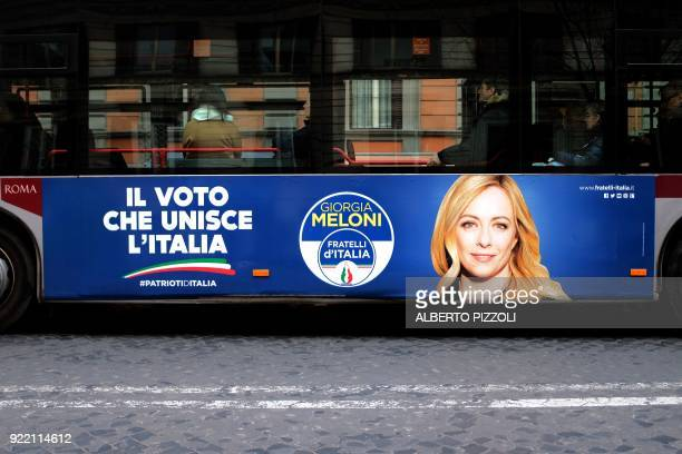 An election poster for the Fratelli D'italia party is seen on the side of a bus in Rome on February 21 2018 ahead of the March 4 general elections...