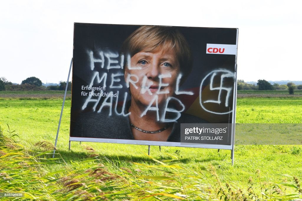 An election poster of German Chancellor Angela Merkel, the Christian Democratic Union's (CDU) main candidate for the chancellorship, that has been sabotaged with a swastika and a text reading 'Heil. Get lost Merkel' is seen in Cuxhaven, northern Germany, on September 10, 2017. /