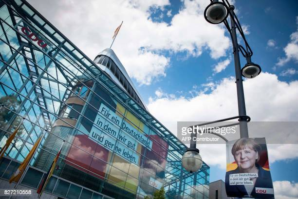 An election poster with the portrait of German Chancellor and leader of Germany's conservative Christian Democratic Union party Angela Merkel hangs...